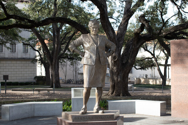 Photo of the Barbara Jordan statue on UT Austin campus. Jordan is standing with her hands on her hips and feet spread apart.